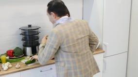 Type affectueux étreignant son amie de sourire dans leur cuisine tôt le matin avec le petit déjeuner étant fait clips vidéos