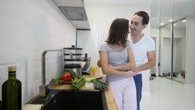 Type affectueux étreignant son amie de sourire dans leur cuisine tôt le matin avec le petit déjeuner étant fait dans le mouvement clips vidéos