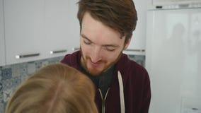 Type affectueux étreignant son amie de sourire dans leur cuisine tôt le matin avec le petit déjeuner étant fait dans le mouvement banque de vidéos