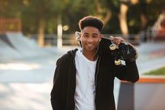 Type africain gai d'adolescent avec des écouteurs Photographie stock