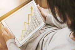 Type asiatique à l'aide du comprimé numérique dans le salon, avec soulever des graphiques de flèche sur l'écran Photo libre de droits