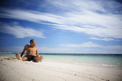 Type asiatique détendant sur la plage Photo stock