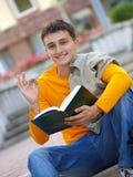 Type attirant avec le livre affichant le geste en bon état photos stock