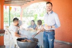 Type attirant faisant cuire des hamburgers à un barbecue Image libre de droits