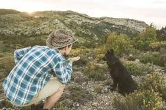 Type au coucher du soleil avec son chien Concept de l'amour entre l'homme et le chien Images stock
