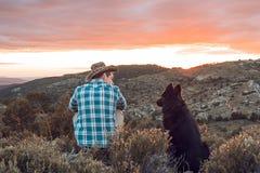Type au coucher du soleil avec son chien Concept de l'amour entre l'homme et le chien Photos libres de droits