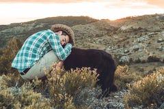 Type au coucher du soleil avec son chien Concept de l'amour entre l'homme et le chien Images libres de droits