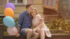 Type avec des ballons à air étreignant son amie, couple caressant la date romantique Photo stock