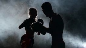 Type avec des gants de boxe de fille battant dans l'anneau dans l'obscurité Silhouette Fumez le fond Mouvement lent banque de vidéos