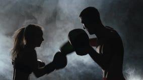 Type avec des gants de boxe de fille battant dans l'anneau dans l'obscurité Silhouette Fumez le fond Mouvement lent clips vidéos