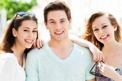 Type avec deux amis féminins photographie stock