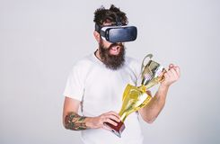 Type avec la concurrence gagnée par verres de VR et le gobelet d'or disponible de prise Le hippie sur le visage heureux a gagné l photo stock