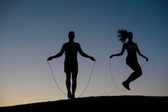 Type avec la fille réchauffant sur une corde à sauter images libres de droits