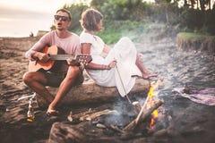 Type avec la guitare et son amie s'asseyant sur le rondin et chantant pour ses amis la soirée d'été par le feu de camp Images stock