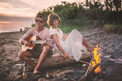Type avec la guitare et son amie s'asseyant sur le rondin et chantant pour ses amis la soirée d'été par le feu de camp Image stock