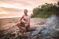 Type avec la guitare se reposant sur le rondin et chantant pour ses amis la soirée d'été par le feu de camp Image libre de droits