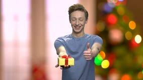 Type avec le boîte-cadeau et le pouce de Noël  banque de vidéos
