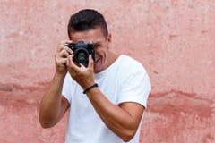 Type avec le rétro appareil-photo dans la chemise blanche devant le backg rose de mur Image stock