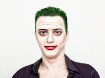 Type avec le visage fou de joker, les cheveux verts et le smike idiot costume carnaval Images stock