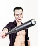 Type avec le visage fou de joker tenant la batte de baseball, les cheveux verts et le smike idiot costume carnaval Image stock