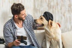 Type avec son ami d'animal familier se reposant à l'intérieur Images stock