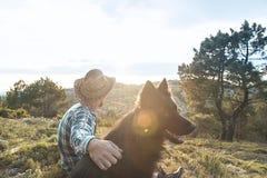 Type avec son chien au coucher du soleil Image libre de droits