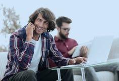 Type avec un ami s'asseyant au bureau Photos libres de droits