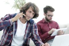 Type avec un ami s'asseyant au bureau Photographie stock libre de droits