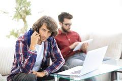 Type avec un ami s'asseyant sur le divan, parlant sur le smartphone et recherchant l'information sur l'Internet Photos libres de droits