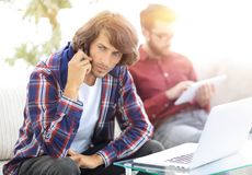 Type avec un ami s'asseyant sur le divan, parlant sur le smartphone et recherchant l'information sur l'Internet Photo stock