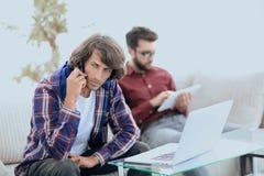 Type avec un ami s'asseyant sur le divan, parlant sur le smartphone et recherchant l'information sur l'Internet Images stock