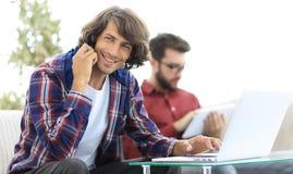 Type avec un ami s'asseyant sur le divan, parlant sur le smartphone et recherchant l'information sur l'Internet Photographie stock libre de droits