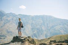 Type avec un sac à dos de voyage sur le dessus d'un rocher Photo libre de droits