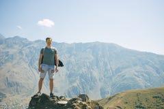 Type avec un sac à dos de voyage sur le dessus d'un rocher Photographie stock libre de droits