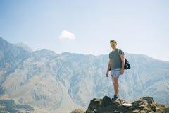 Type avec un sac à dos de voyage sur le dessus d'un rocher Images libres de droits