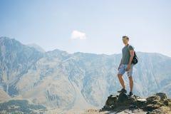 Type avec un sac à dos de voyage sur le dessus d'un rocher Photographie stock