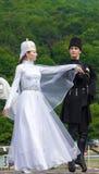 Type avec une fille dans des costumes nationaux d'Adyghe dansant la danse traditionnelle Image libre de droits