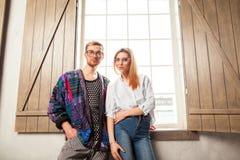Type avec une fille posant dans le studio près de la fenêtre, étable de Vogue Photos stock