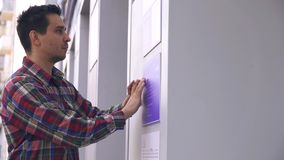 Type aveugle sur la rue lisant une police de Braille sur un signe de bâtiment clips vidéos