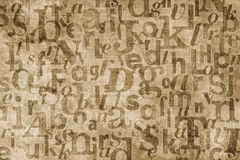 Type background. Grainy and gritty background image made of letters from old newspapers superimposed on eachother Stock Image