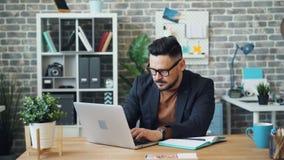 Type barbu à l'aide de l'ordinateur portable au travail écrivant alors l'information dans le carnet banque de vidéos