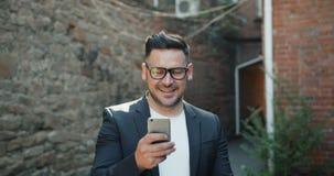 Type barbu beau à l'aide du smartphone textotant dehors dans la rue banque de vidéos