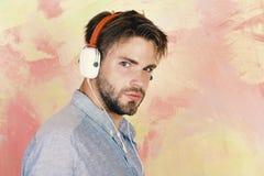Type barbu beau américain avec des écouteurs Mode de vie musical Hippie élégant observé par bleu avec le smartphone photos stock