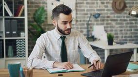 Type barbu employant l'écriture de dactylographie d'ordinateur portable dans le carnet se reposant à la table dans le bureau banque de vidéos