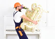 Type barbu fort de vue de côté portant le vieux fauteuil devant le piano Moteur marchant avec le vieux meuble fragile Photo libre de droits