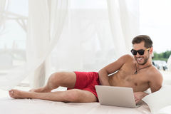 Type barbu jeune gai communiquant par l'intermédiaire de l'instrument sur la station de vacances Image stock