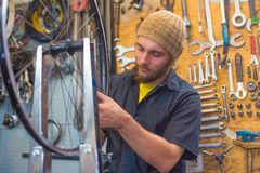 Type barbu réparant la bicyclette dans l'atelier images libres de droits