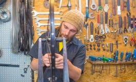 Type barbu réparant la bicyclette dans l'atelier images stock