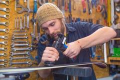 Type barbu réparant le ski dans l'atelier photographie stock