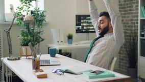 Type barbu travaillant avec l'ordinateur portable étirant alors des bras détendant dans le bureau banque de vidéos